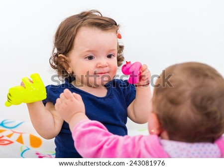 Photo of two adorable baby playing with toys - stock photo