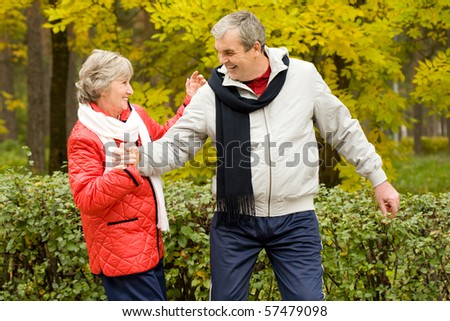 Photo of two aged people having fun during walk in autumn forest - stock photo