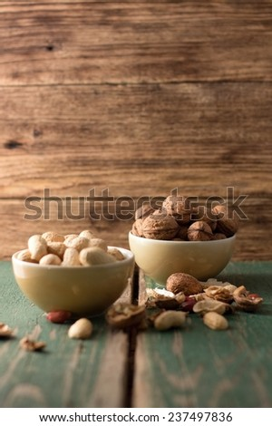 Photo of two bowls, one with walnuts and second with peanuts and with shells and nuts around. Everything is placed on green worn wooden board and with another board in background. - stock photo