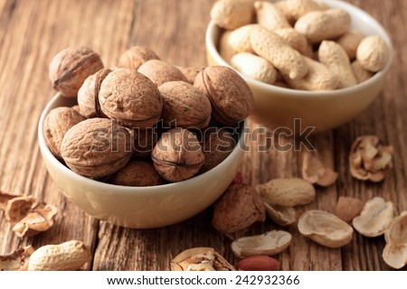 Photo of two bowls, one with walnuts and second with peanuts placed on old worn wooden table with shells and nuts around. - stock photo