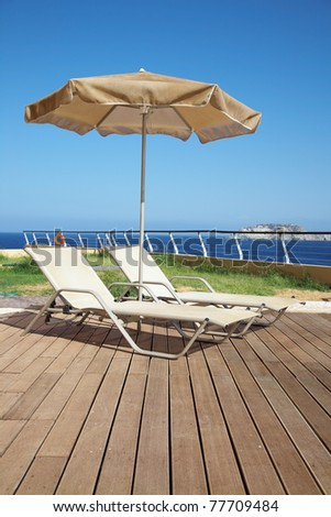 Photo of two deck-chairs with umbrella on the seascape - stock photo