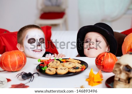 Photo of two eerie boys looking at cookies on Halloween table  - stock photo