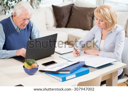 Photo of two elderly people having work at home - stock photo