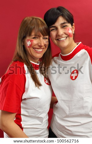 Photo of two female Swiss sports fans smiling and cheering for their team. - stock photo