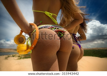 Photo of two girls in bikini on sandy dunes with headphones tanning in the bright summer sun - stock photo