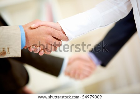 Photo of two handshakes of business partners