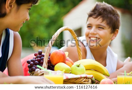 Photo of two happy boy on picnic in park, brothers lying down on meadow and enjoying fresh sweet fruits, teens have lunch outdoors, cheerful male children laughing, healthy lifestyle