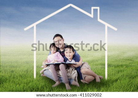 Photo of two happy children and their father smiling at the camera while sitting under a house symbol on the meadow - stock photo