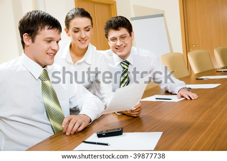 Photo of two men sitting at table and looking at document in secretary?s hand during meeting