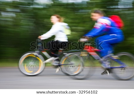 Photo of two people riding their bicycles outdoors - stock photo