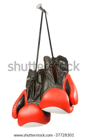 Photo of two red boxing gloves 12 oz hanging on a nail, on a black cord, on a white wall. Studio isolation on white background.