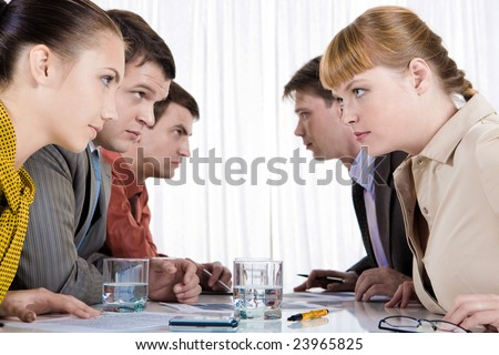Photo of two rows of business people looking at each other with tension - stock photo