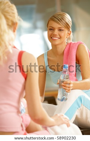 Photo of two teenage girls sitting in the sports gym and communicating