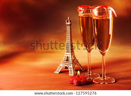 Photo of two wine glass decorated with red ribbon, heart-shaped candle and small Eiffel tower, beverage still life, Valentine day in Paris, dark grange background, love and romance concept - stock photo