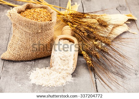Photo of wheat grains and flour on the wooden table