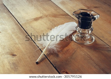photo of white Feather and inkwell on old wooden table  - stock photo