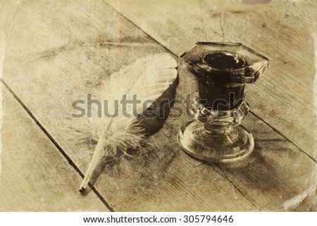 photo of white Feather and inkwell on old wooden table. retro filtered image, black and white style photo - stock photo