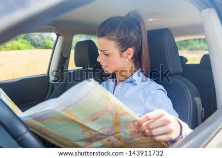 photo of woman looking at a map inside her car