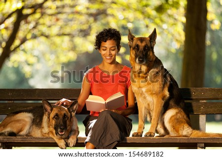Photo of woman sitting on a bench with two german shepherds - stock photo