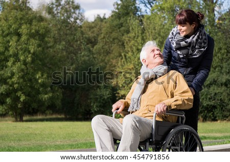 Photo of woman supporting elderly man on wheelchair  - stock photo