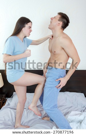 Photo of young angry woman in panties kicking with leg handsome half naked man in groin or genitals with painful face expression. Defense against sexual assault in bedroom. Fight against violence. - stock photo