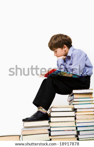 Photo of young boy reading a manual while sitting on top of book stack