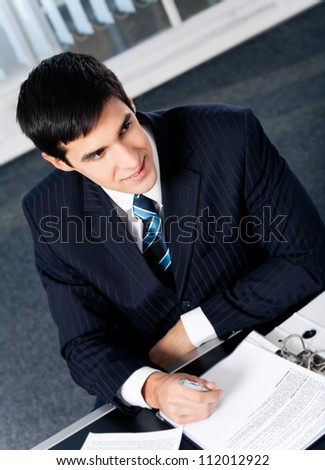 Photo of young business man writting at office