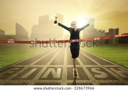 Photo of young business woman winning the race competition and crossing the finish line while carrying a trophy - stock photo