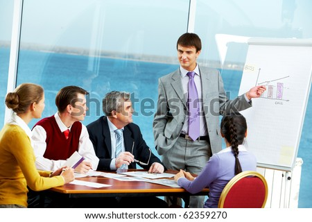 Photo of young businessman standing near board and pointing at graph of growth company