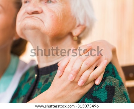 Photo of young caregiver hugs the elderly woman - stock photo