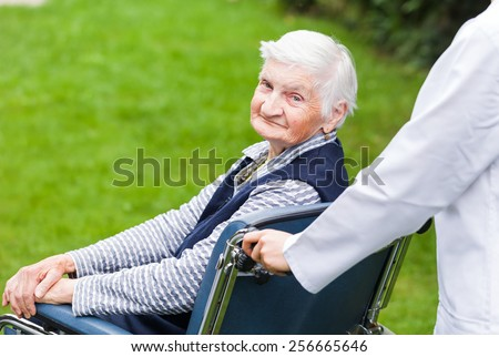 Photo of young carer pushing the elderly woman in wheelchair  - stock photo