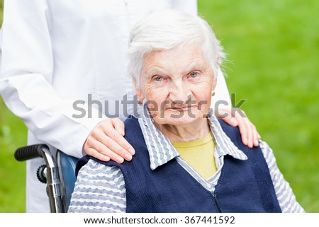 Photo of young carer pushing the elderly woman in wheelchair