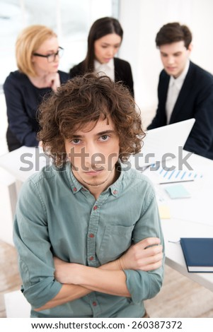 Photo of young casual businessman looking at camera with his business team on background. Office interior with window. Concept for teamwork