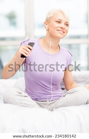 photo of young caucasian woman sitting on a bed and shaking while listening music with headphones  - stock photo