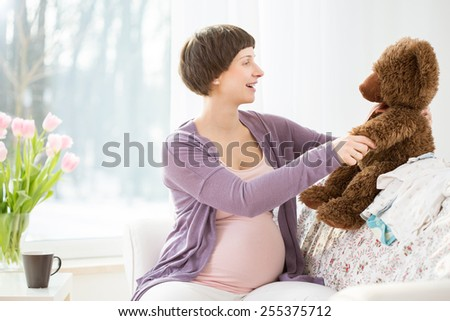Photo of young cheerful pregnant woman with cute teddy bear - stock photo