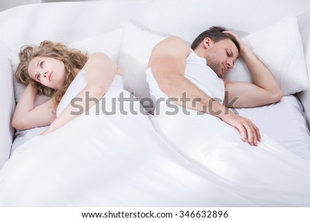 Photo of young couple in crisis lying in bed - stock photo