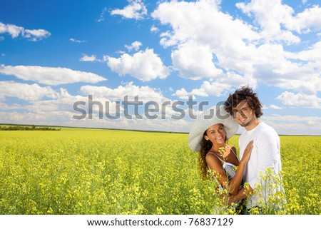 Photo of young couple standing on field and hugging each other while looking at camera