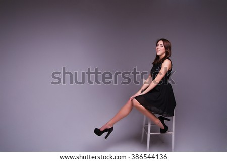 photo of Young elegant woman in black  dress, shoes. Sitting and posing in studio