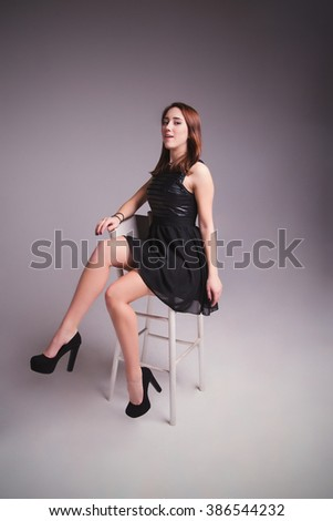 photo of Young elegant woman in black  dress, shoes. Sitting and posing in studio - stock photo