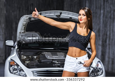 Photo of young female car repair worker. Glamour sexy brunette wearing jean shorts. Girl with wrench looking at camera, standing near car cowl and making hitchhiking gesture - stock photo