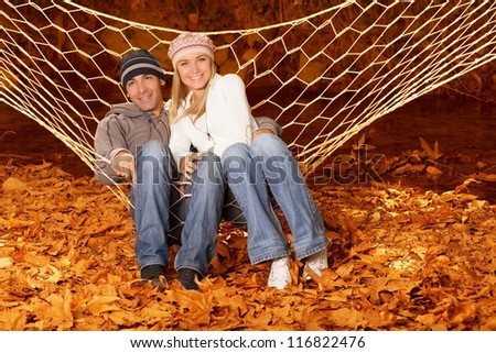 Photo of young happy family lying down in hammock on backyard - stock photo
