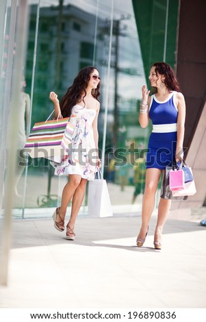 Photo of young joyful girls with shopping bags on the background of shop windows - stock photo