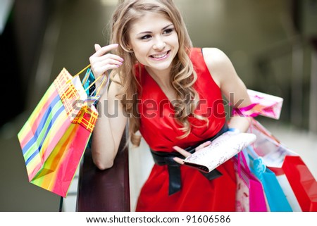 Photo of young joyful woman with shopping bags on the background of shop windows - stock photo