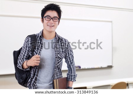 Photo of young male student standing the classroom while smiling at the camera - stock photo