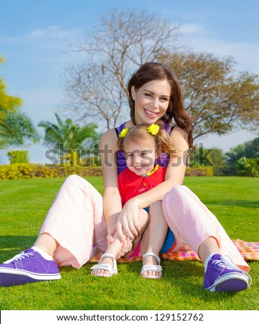 Photo of young mother with cute little daughter sitting down on green grass field in park, beautiful woman with small pretty girl having fun outdoors in spring, happy family on picnic, love concept - stock photo