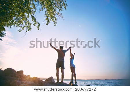 Photo of young sporty couple standing on the coastline with raised arms - stock photo