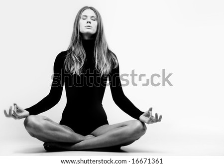 Photo of young woman sitting in pose of lotus and meditating - stock photo