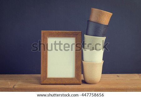 Photo old wood frame with stacked 5 cups on old wooden table, black background. Emphasizing copy space for write text. image style vintage. - stock photo