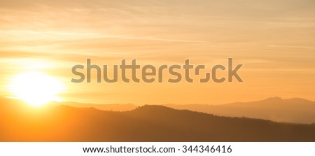 Photo panorama of beautiful surrealistic spectacular orange sunset behind mountain range over cloudy sky with fog on ridge silhouette background, horizontal picture - stock photo
