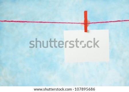 photo paper hanging on the clothesline on light blue background